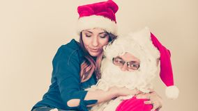 Santa Claus hugging woman with christmassy hat stock photo
