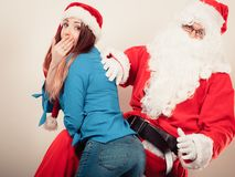 Santa Claus spanking woman with christmassy hat Stock Photos