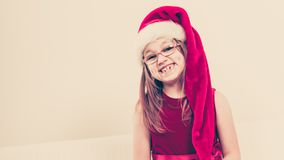 Smiling christmas girl in santa hat festive outfit royalty free stock photos