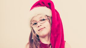 Christmas girl in santa hat festive outfit. Christmas holiday concept. Toddler girl wearing Santa Claus hat and christmassy dress Royalty Free Stock Photography