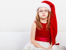 Christmas girl in santa hat festive outfit. Christmas holiday concept. Toddler girl wearing Santa Claus hat and christmassy dress Stock Photos