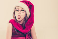 Girl in santa hat making silly face Royalty Free Stock Images