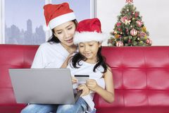Mother and child with credit card. Christmas holiday concept. Young mother and her daughter shopping online with a credit card and laptop at home Stock Image