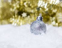 Christmas holiday conceptual image with silver glitter decoration in front of golden tinsel. Silver glitter christmas decoration on fake snow with golden tinsel stock photos