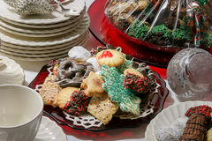 Christmas holiday cookies with plates ad silverware. The table is being set for Christmas. Stollen and cookies in a cozy setting with white chin and decorations royalty free stock images