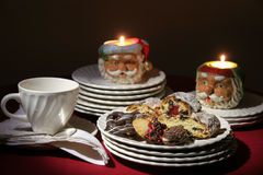 Christmas holiday cookies with plates and candles. The table is being set for Christmas. Stollen and cookies in a cozy setting with candles and white china stock image