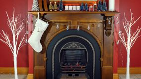 Christmas holiday decorated mantelpiece and fire place. Cosy Christmas holiday decorated mantelpiece and fire place in red and white theme Royalty Free Stock Image