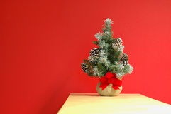 Christmas holiday decoration (horizontal). Little frosty pine with cones, christmas holiday decoration on a vibrant red background Stock Images
