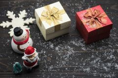Christmas holiday decoration on wooden background. Christmas holiday season wooden background with winter decoration of snow flake, xmas gift boxes, snowman, and stock photography