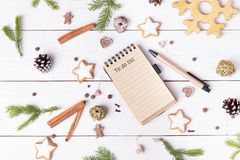 Christmas holiday decorations and notebook with to do list on white vintage table from above, christmas planning concept royalty free stock image