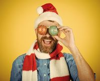 Christmas holiday decorations and ornaments. Man cover eyes with xmas balls on yellow background. New year celebration. Hipster happy smile in santa hat and stock photography