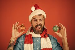 Christmas holiday decorations and ornaments. Man hold xmas balls on red background. New year celebration. Hipster wink in santa hat and scarf. Spirit, joy royalty free stock photography