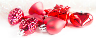 Christmas holiday decorations, red heart, pine cone, bell, gift on white background with copyspace Stock Images