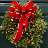 Christmas holiday decorative garland with a big red and gold bow Royalty Free Stock Photo