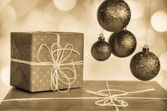 Christmas holiday details. Close up of New Year decorations, balls and presents isolated on beautiful background. Horizontal toned in sepia color photo Stock Images