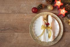 Christmas holiday dinner place setting - plates, napkin, cutlery, gold bauble decorations over oak table background. Fork and. Spoon on gold plates. Around red royalty free stock photography