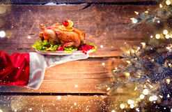 Christmas holiday dinner. Santa`s hand holding roasted chicken Stock Photos