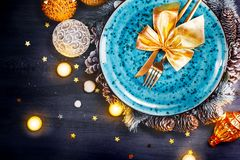 Christmas holiday dinner table setting. Xmas table decoration with blue plate, colorful decor and candles stock images