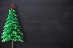 Christmas holiday empty background as copy space with origami handmade Christmas tree isolated on the left royalty free stock photo