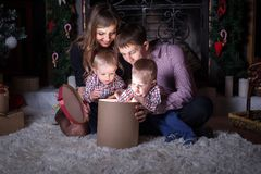 Christmas holiday. Family opens the magic box with gift. stock photos