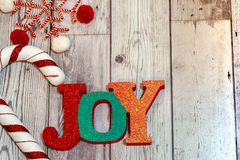Christmas holiday flatlay with sparkle glittery Joy word in red. Plaid, decorative candy cane and a twine snowflake. Useful for rustic backgrounds stock photos