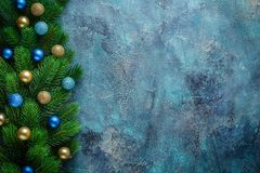 Christmas holiday frame with festive decorations blue and gold baubles on old blue background. Christmas background with copy