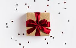 Christmas holiday gift box red bow on decorated festive table with sparkle stars. On white background. Packaging gift wrap and ribbons. Winter time new year stock photo