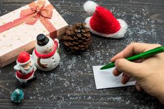 Christmas holiday with hand writing card on wood. Christmas holiday season wooden background with winter decoration of pine cones, snow, xmas gift boxes, snowman stock photography