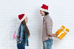 Christmas Holiday Happy Couple Hold Surprise Present Boxes Wear New Year Santa Hat Cap, Man And Woman Smiling Royalty Free Stock Images
