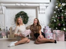 Christmas holiday happy girl friends exchanging presents in christmas decorated living room. stock photography
