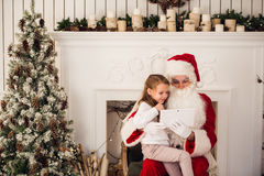 Christmas holiday happy girl santa looking at something on digital touch screen tablet PC, over chimney and tree Stock Image
