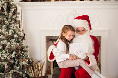 Christmas holiday happy girl santa looking at something on digital touch screen tablet PC, over chimney and tree Stock Photo