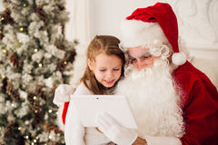 Christmas holiday happy girl santa looking at something on digital touch screen tablet PC, over chimney and tree Stock Photography
