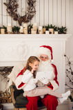 Christmas holiday happy girl santa looking at something on digital touch screen tablet PC, over chimney and tree Royalty Free Stock Photos