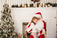 Christmas holiday happy girl santa looking at something on digital touch screen tablet PC, over chimney and tree Royalty Free Stock Image