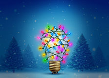 Christmas Holiday Inspiration. As a winter forest background with a lightbulb decorated with bright glowing lights as a creative celebration idea  for the new Royalty Free Stock Image