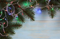 Colorful garland on spruce branches. Christmas, holiday, lights, background, year, garland, xmas, new, festive, decoration, white, celebration, winter, happy royalty free stock photography