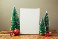 Christmas holiday mock up with canvas and pine tree on wooden table Royalty Free Stock Image
