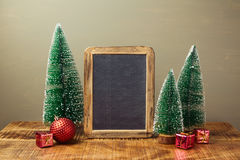 Christmas holiday mock up with chalkboard and pine tree on wooden table Royalty Free Stock Photo