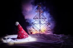 Christmas holiday New Year background with Santa Clause hat and blurred Christmas tree on snowy background. New Year conceptual im Royalty Free Stock Image