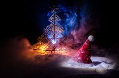 Christmas holiday New Year background with Santa Clause hat and blurred Christmas tree on snowy background. New Year conceptual im Royalty Free Stock Images