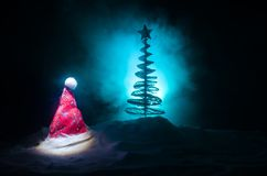 Christmas holiday New Year background with Santa Clause hat and blurred Christmas tree on snowy background. New Year conceptual im Royalty Free Stock Photos