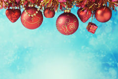Christmas holiday ornaments hanging over blue bokeh background with copy space Royalty Free Stock Photo