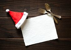 Christmas Holiday Paper Card with Red and White Santa Claus Hat and fork and spoon on Dark Rustic Wood Table Background.