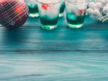 Christmas holiday party background with drinks. Christmas holiday party background with green alcohol drinks with cherry. Festive aperitif shots and ornaments on royalty free stock image