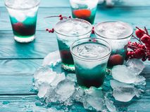 Christmas holiday party green and red drinks. Christmas holiday party green alcohol drinks with cherry. Festive aperitif shots and ornaments on wooden dark table stock photography