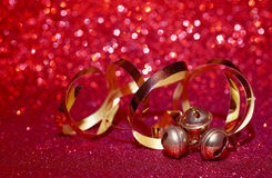 Christmas holiday red background, three small bells Royalty Free Stock Image
