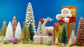 Christmas holiday setting with vintage Santa music box and ornaments. Christmas holiday table with vintage Santa jack in the box and Christmas tree and reindeer royalty free stock image