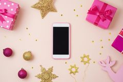 Christmas holiday smart phone mock up, pink gift boxes and decor stock photos