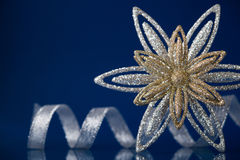 Christmas holiday snowflake and silver ribbon on dark blue background. With space for text royalty free stock photography